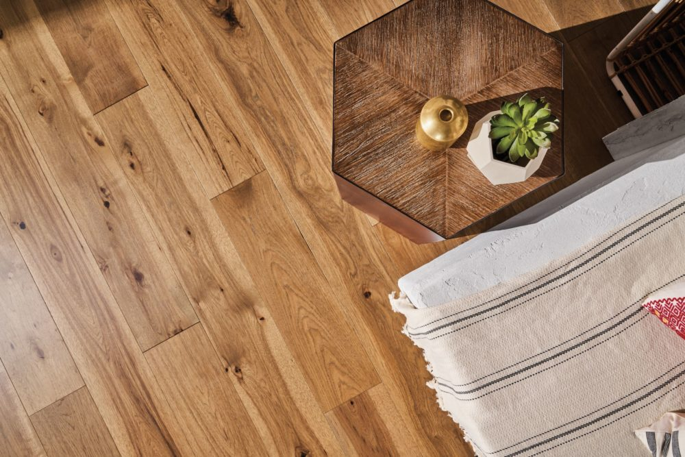 Image looking down at a hardwood floor. There is a coffee table with a succulent and gold vase next to a white concrete bench covered with a striped throw. The floor is a warm, high variance wood floor with light streaking throughout and dark knotting.
