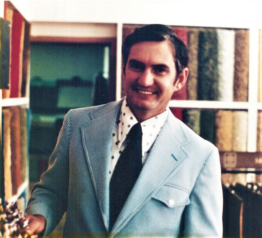 The Carpet Shoppe's owner, Dale, smiles in the showroom in the 1980s.