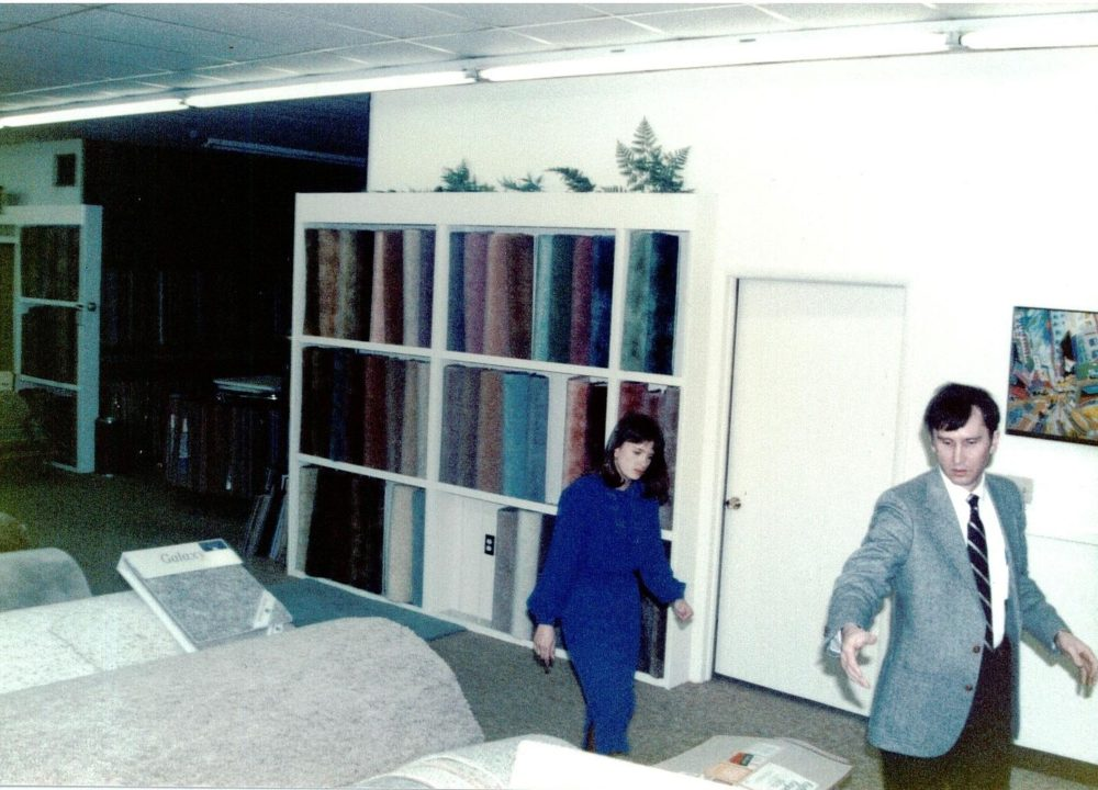 The Carpet Shoppe's employee, Dennis, shows a customer around the showroom in the 1980s.