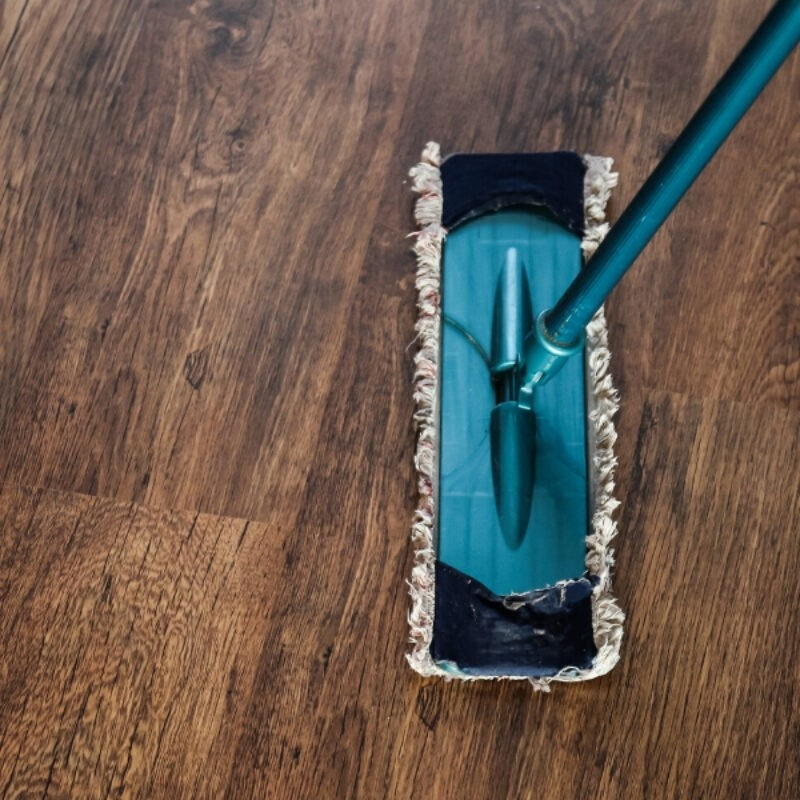 An image looking down on a dark brown hardwood floor with a blue dust mop in the center right of the image