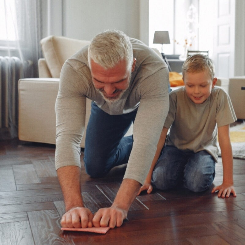 An image of a father and son kneeling on a herringbone floor with a cleaning rag in hand
