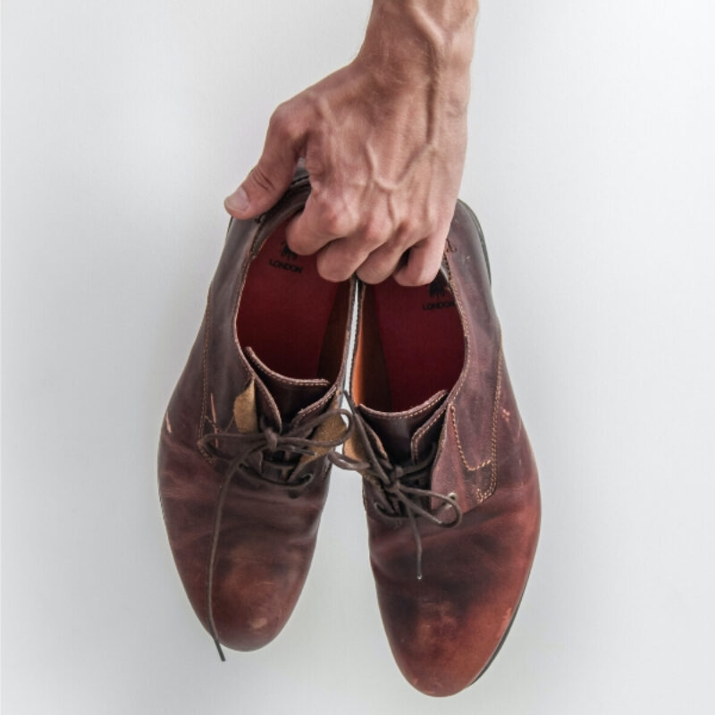 An image of a mans hand holding a pair of leather shoes in front of a white wall