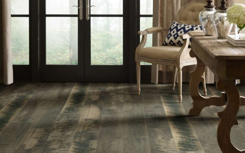 A room scene with a reclaimed wood look floor in a gray washed color. There are large black double doors in the background of the image looking out into a foggy woodsy scene. The furniture in the room is traditional and light in color.