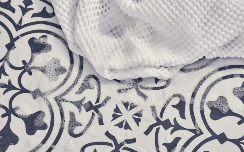 A close up image of decorative navy and white flooring with soap suds and a white wash cloth.