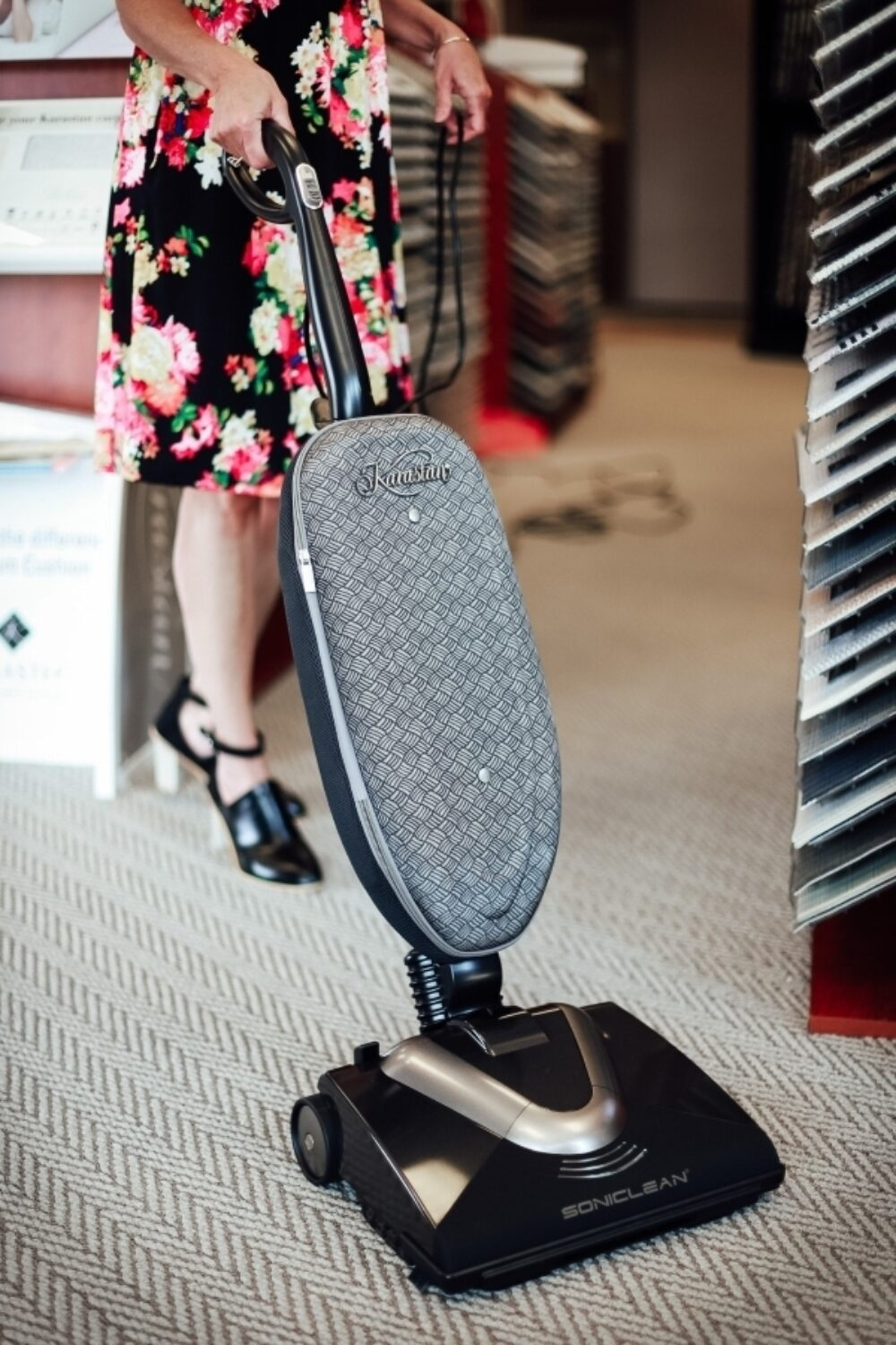 An image of a woman in a floral dress using the Karastan Soniclean vacuum on a woven look carpet. There are carpet display stands behind her.